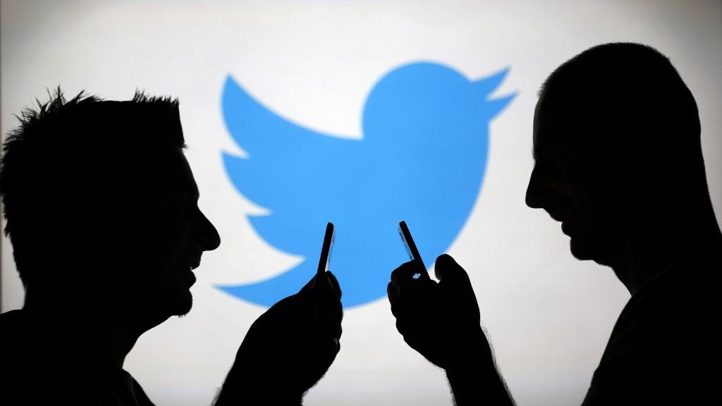 Pengguna ponsel sedang berada di depan logo Twitter. Sumber foto: today.com